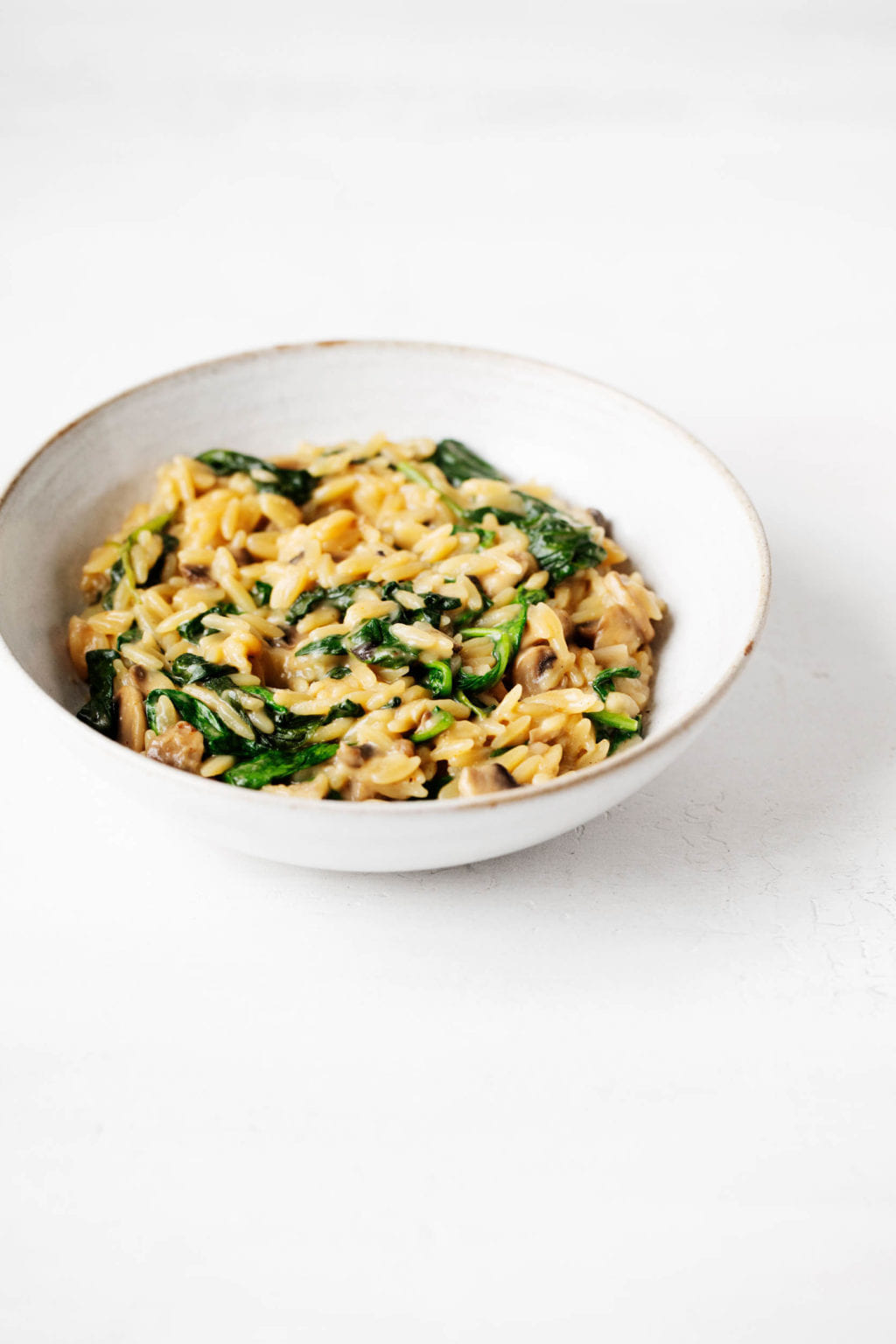 A white bowl with a light brown rim has been filled with a mixture of small pasta and green vegetables.
