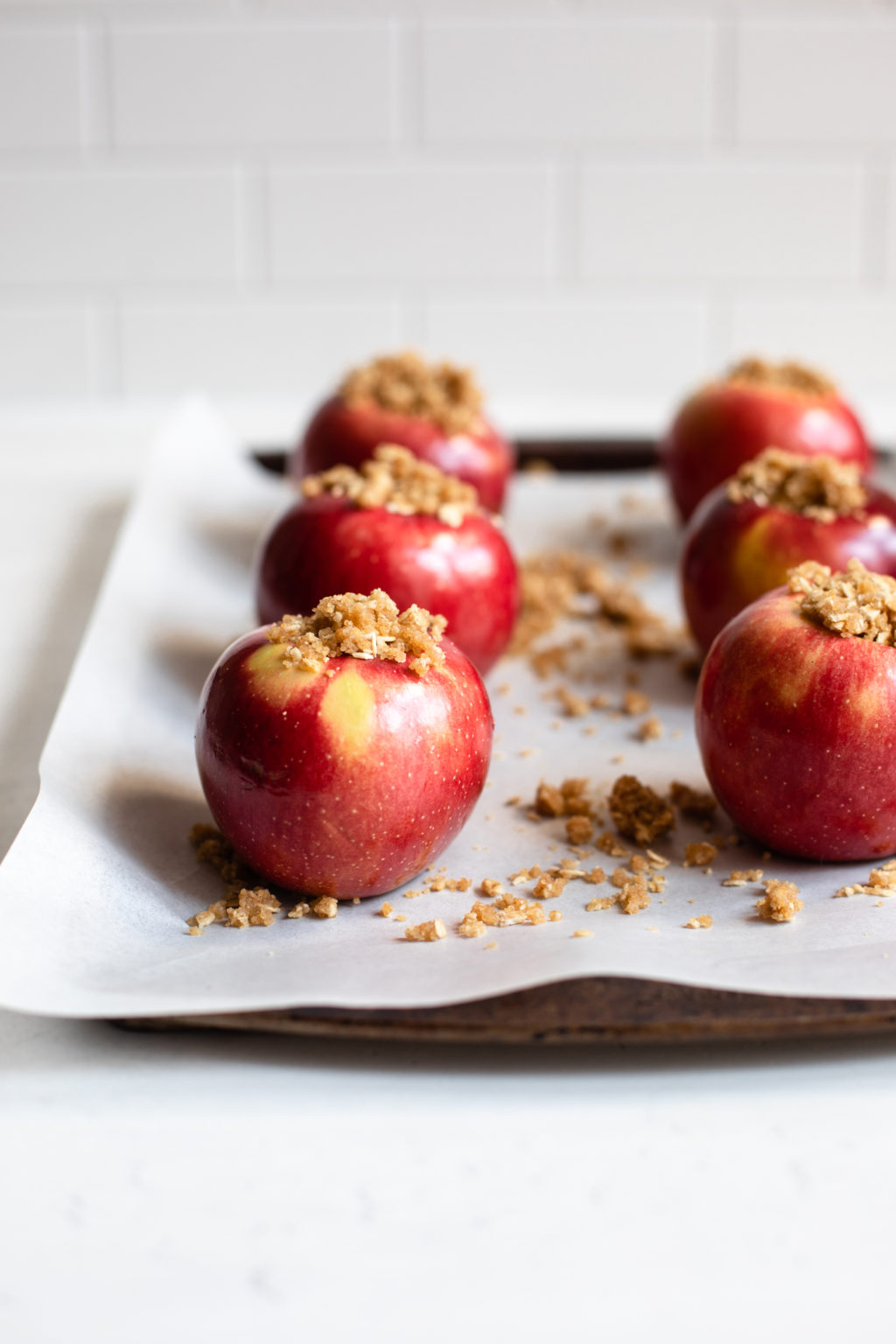The baking sheet is covered with parchment paper and bright red apples, stuffed with oats, flour and brown sugar.