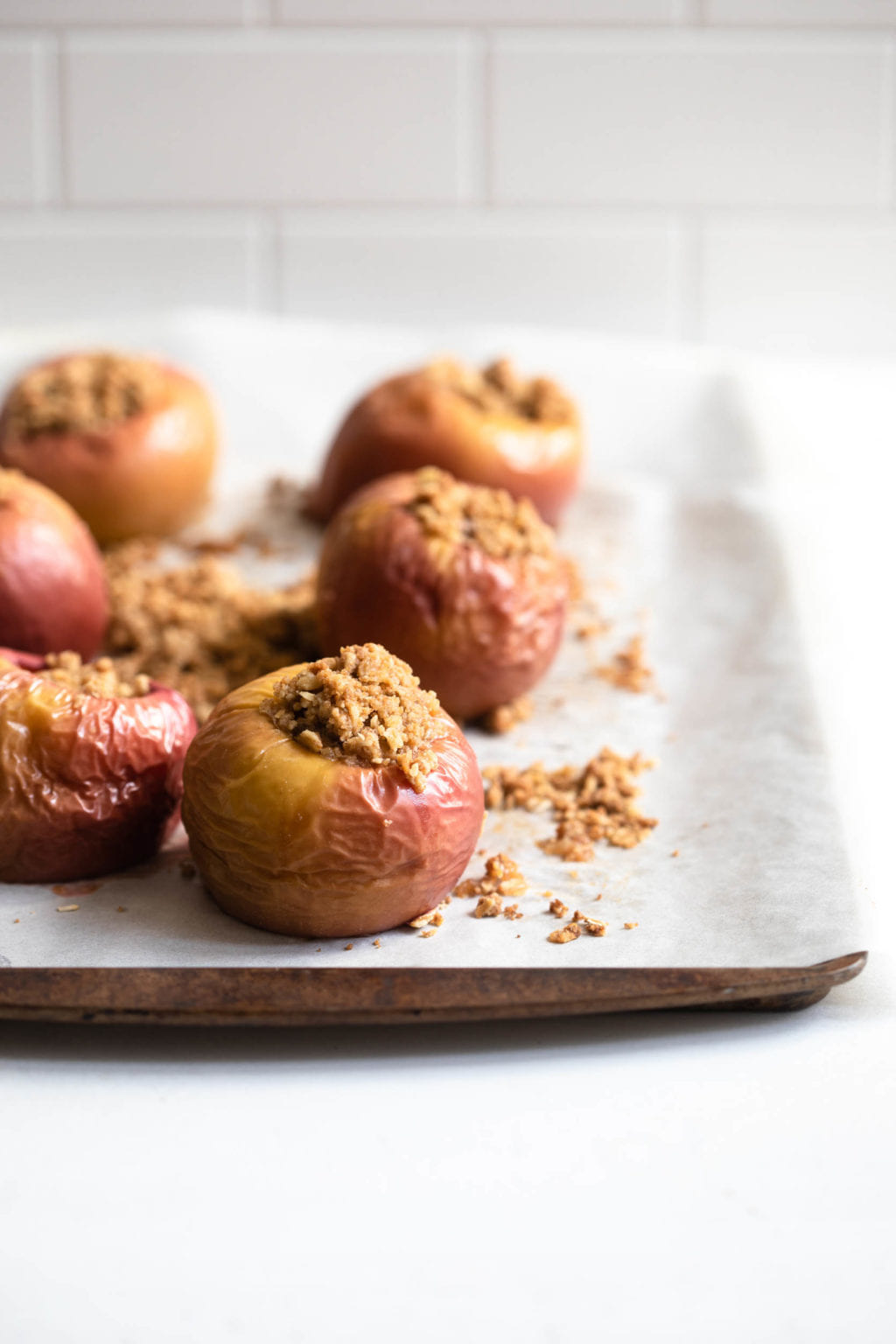 A baking sheet lined with parchment paper can hold six baked apples, and the parchment paper has crumbles of powdered sugar and butter.