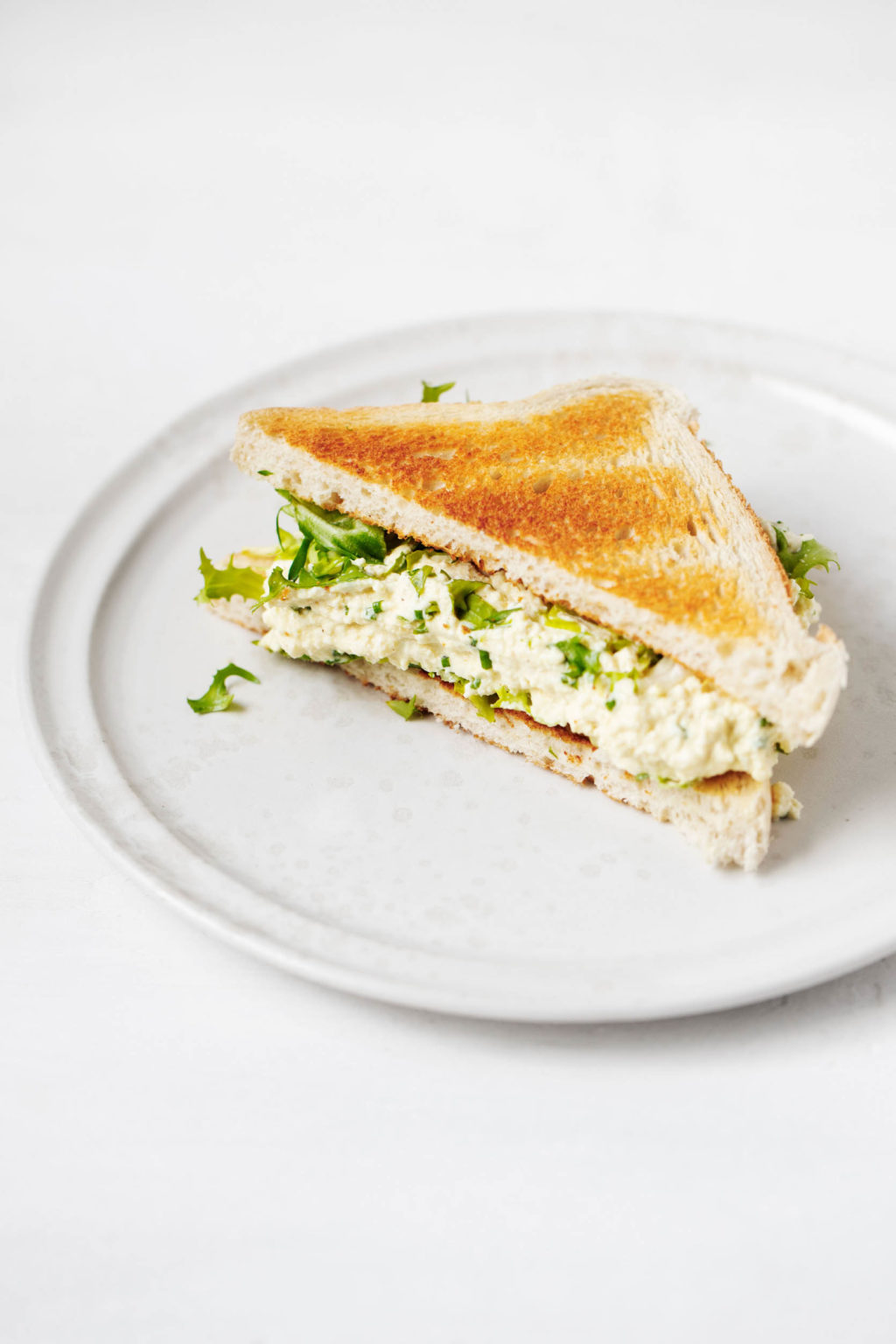 An angle photo of a white plate with half of tofu egg salad sandwich and fresh vegetables on it.