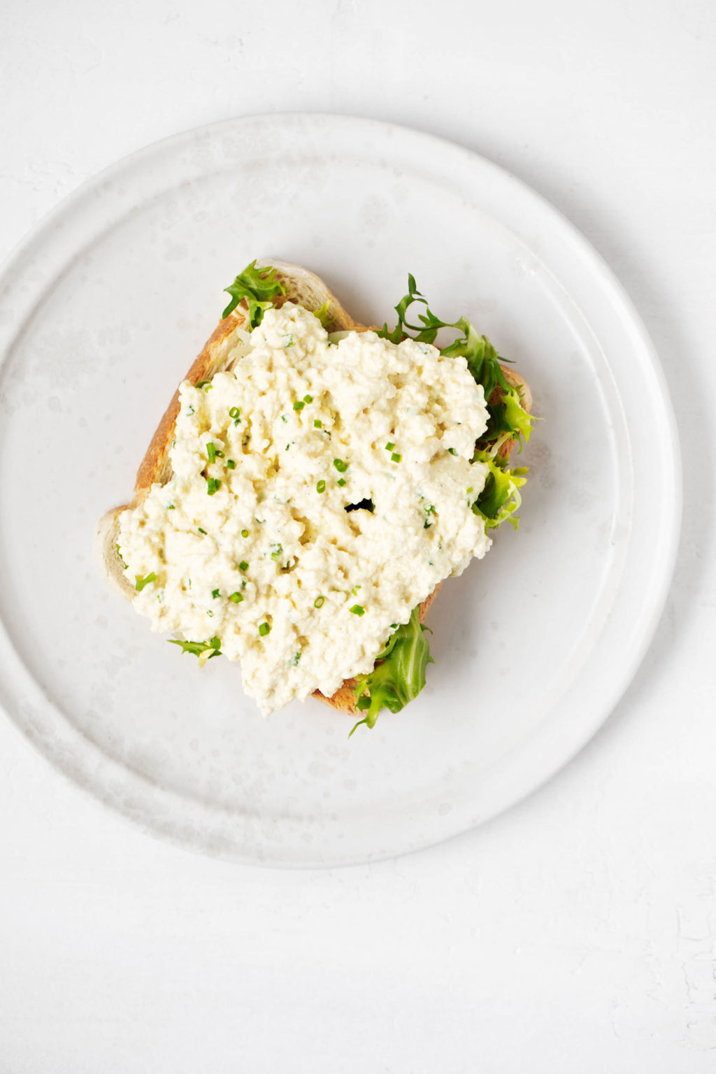 A slice of vegan tofu and egg salad and a slice of green lettuce covered a slice of toast. It is placed on a white ceramic plate.