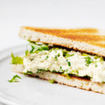I have prepared a grilled sandwich with a vegan tofu and egg salad. It is plated on a white ceramic plate.