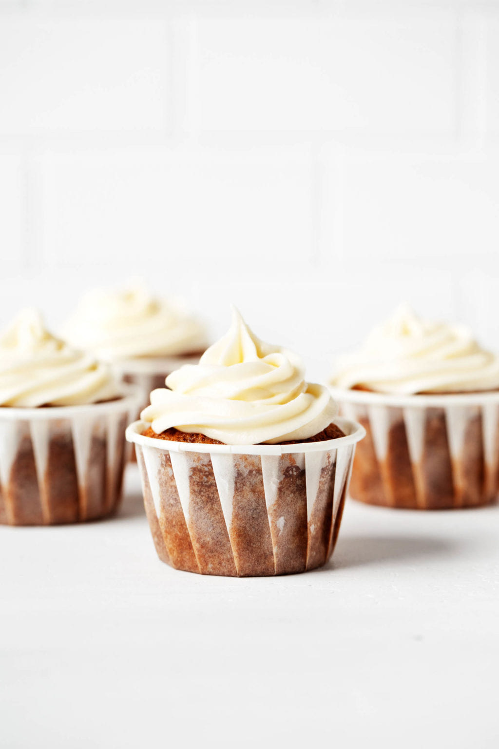 On a bright background, frosted vegan carrot cake cupcakes are lined up in a row.