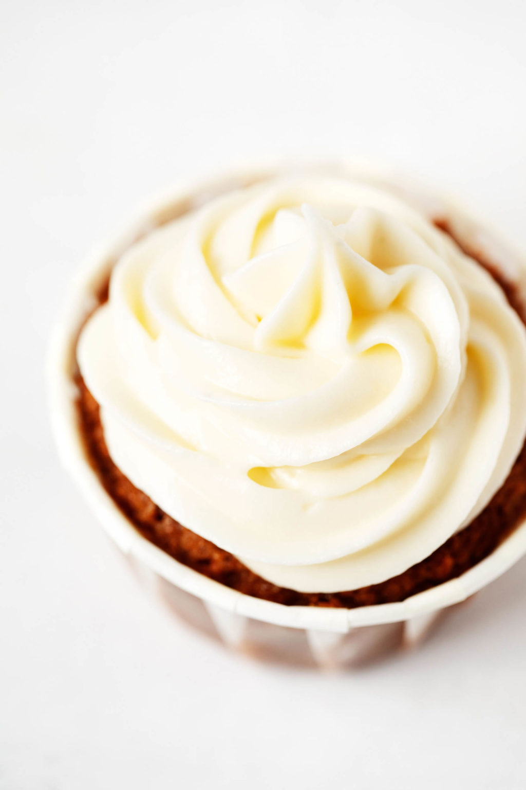A vegan cupcake has been swirled with a rich, pale colored cream cheese frosting.