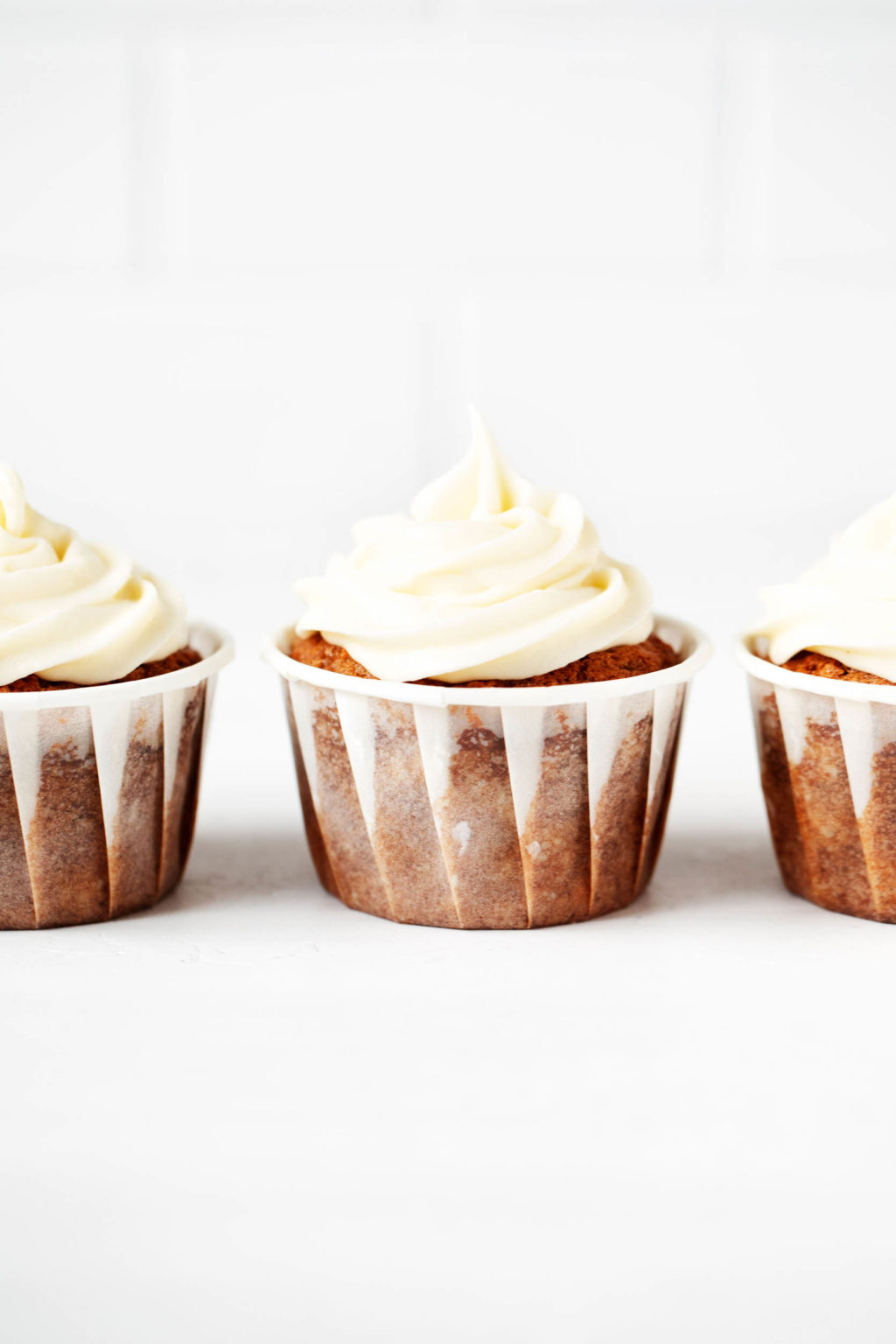 Three vegan cupcakes, made with carrots and cream cheese frosting, are lined up neatly in front of a white brick surface.