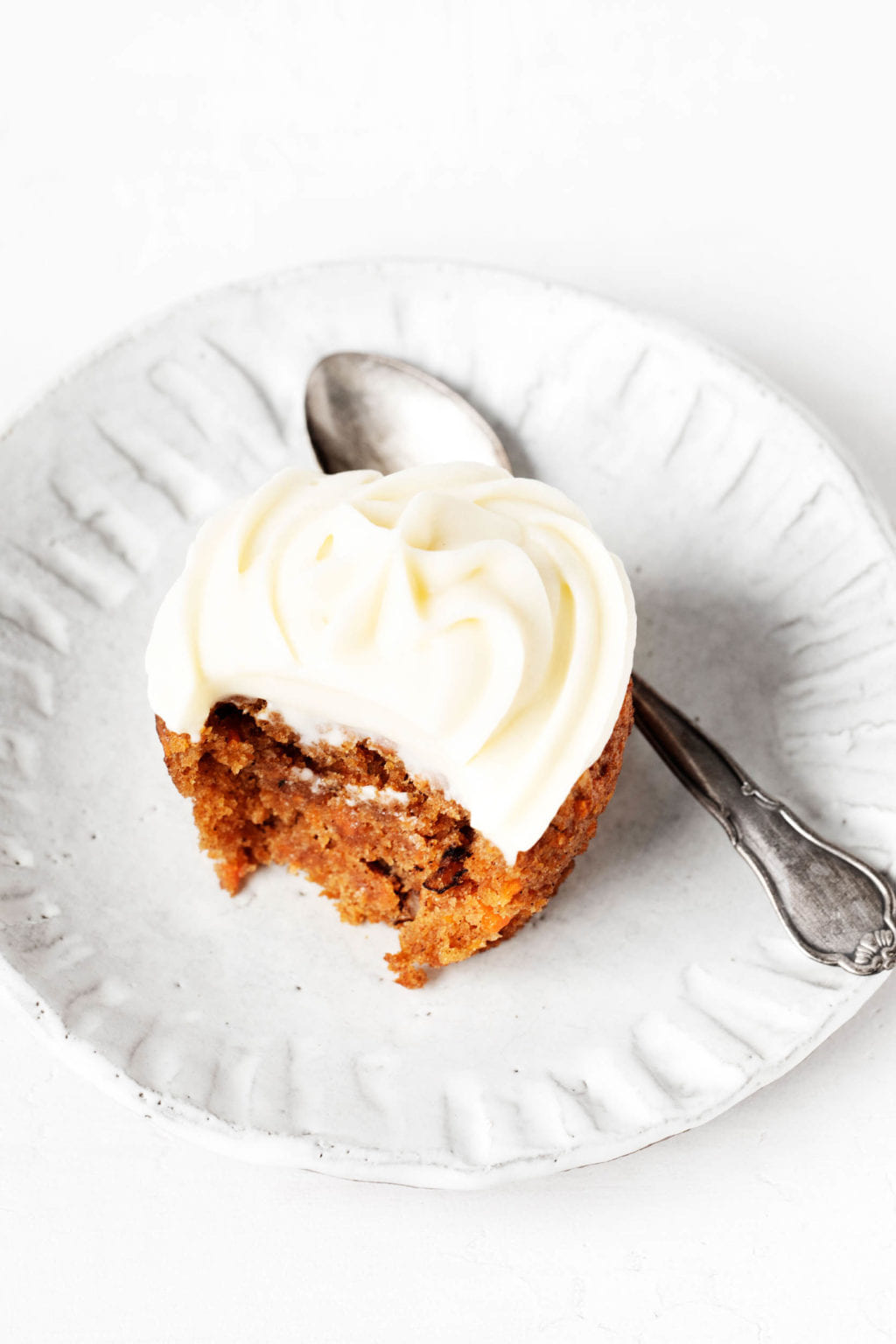 A vegan carrot cake cupcake is placed on a small ceramic white plate. There is a small spoon next to the cupcakes.
