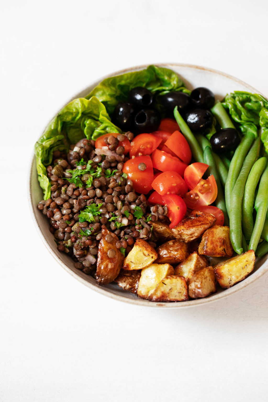 A white bowl is filled with cooked French lentils, baked potatoes, tomatoes, olives and green beans.