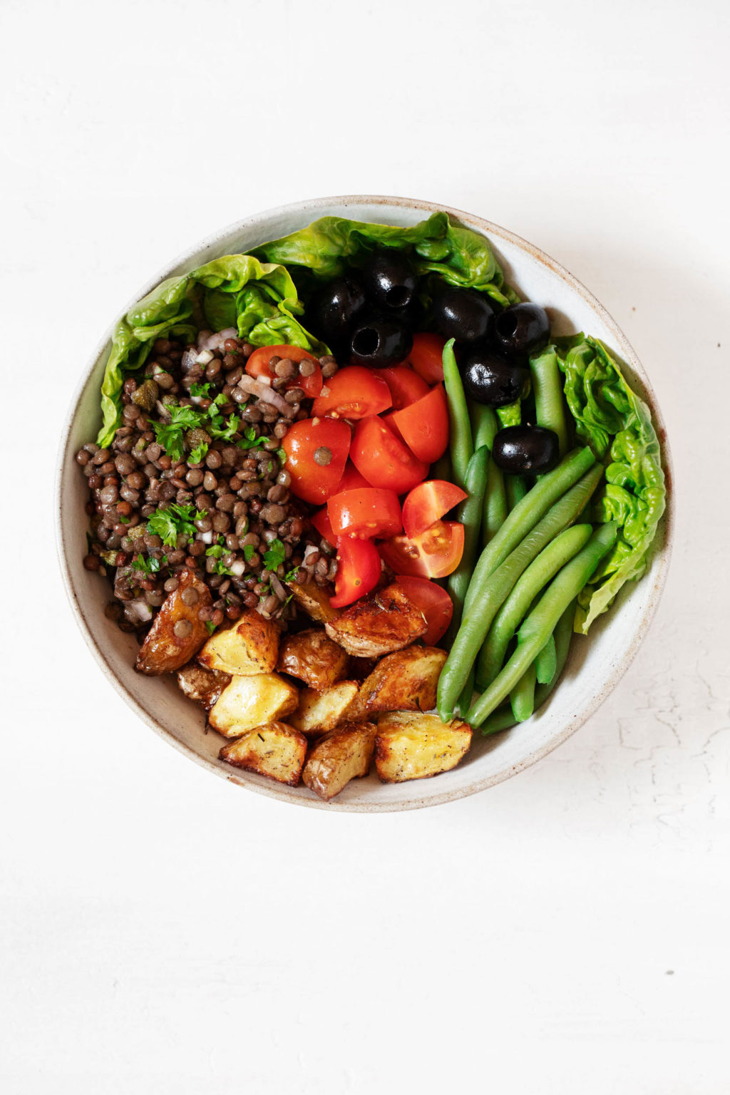 An overhead image of a bowl of plant-based salad, which has been made with green beans, tomatoes, olives, and butter lettuces.