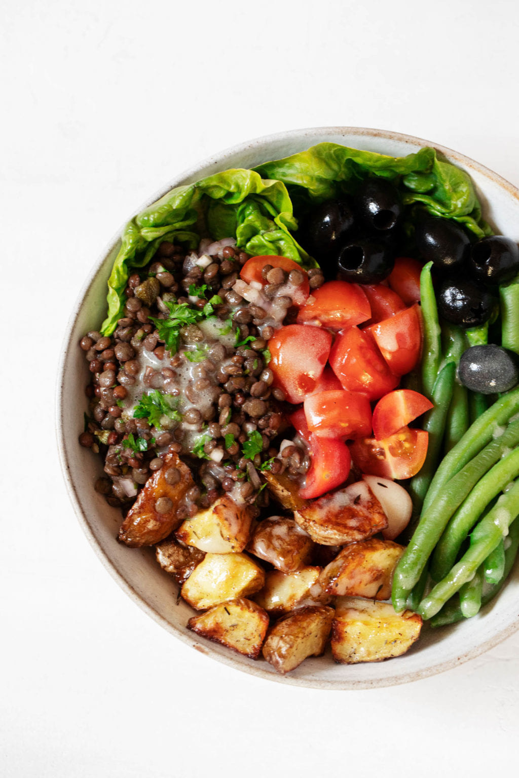 A round white salad bowl contains colorful ingredients for making Niçoise vegetarian salads, including tomatoes, lentils, potatoes and green beans.