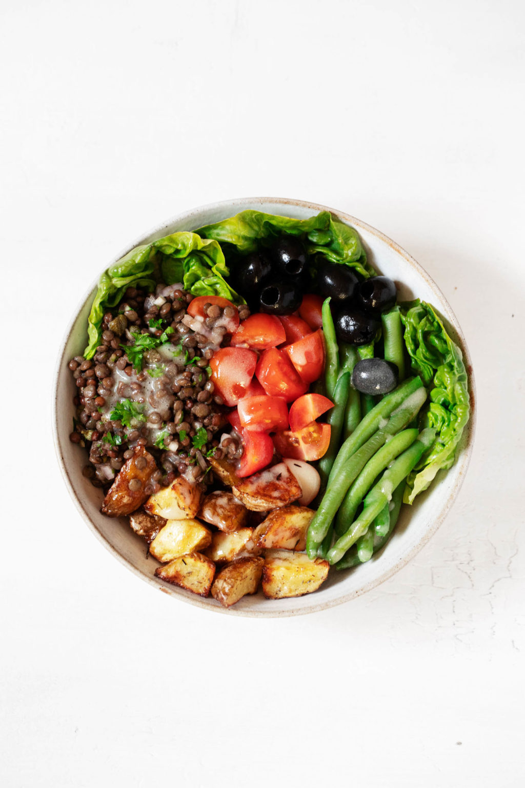 An overhead photograph of a composed salad, which has been made with an array of colorful plant-based ingredients.