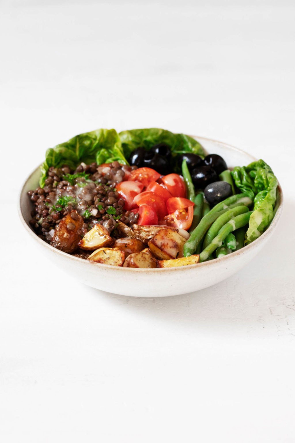 An angled photograph of a round bowl of vegan lentil Niçoise salad, which is resting on a clean white surface.