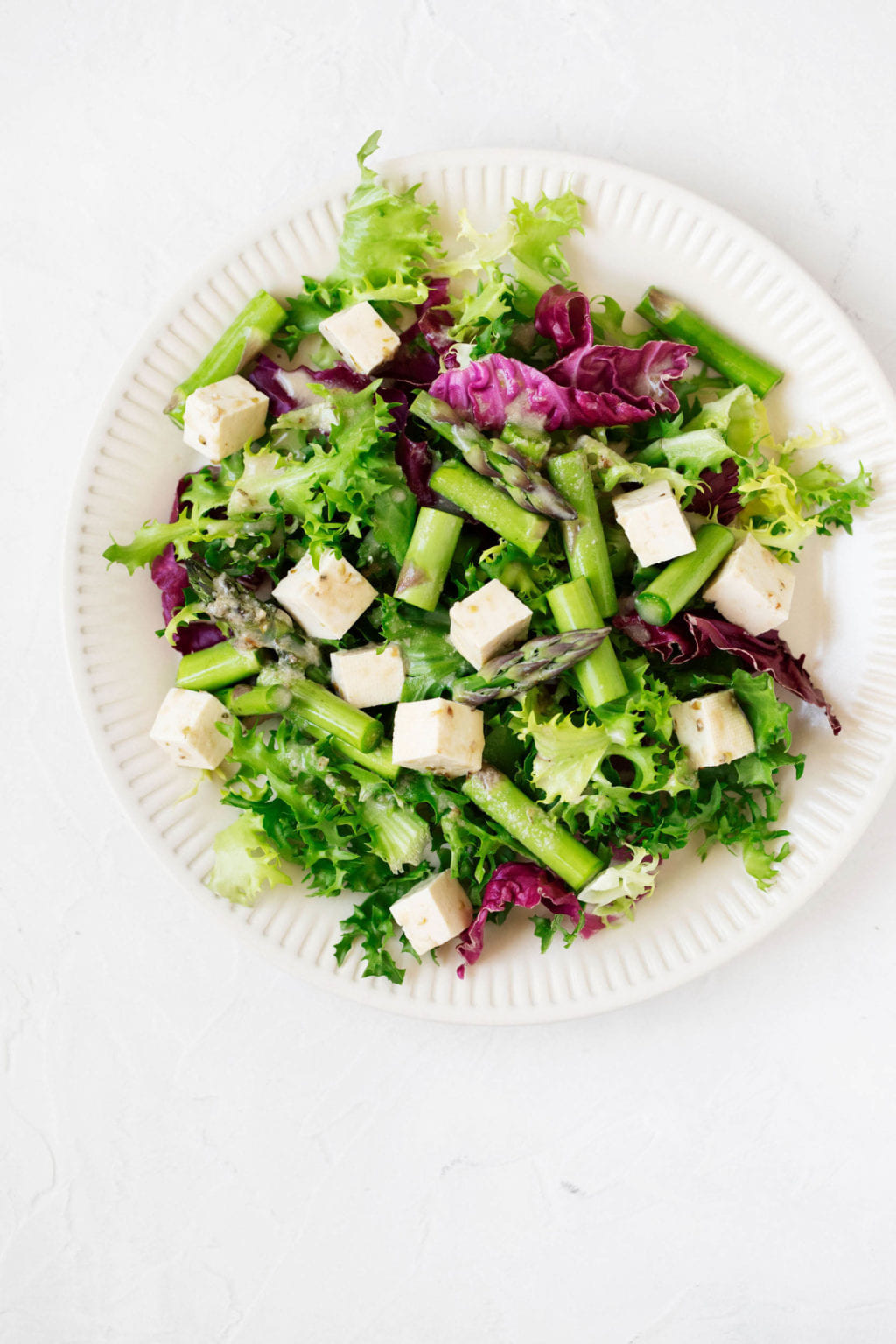 A bright, vibrant spring salad is served on a white, fluted ceramic plate. A marinated tofu mixture is part of the salad.