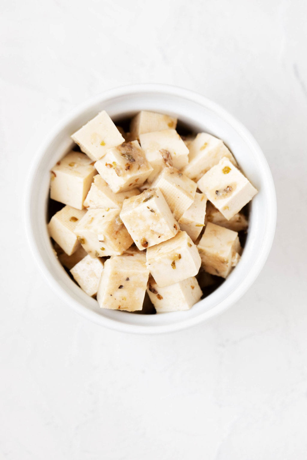 A small white round ramekin is filled with pieces of marinated tofu and dried herbs. It sits on a white background.